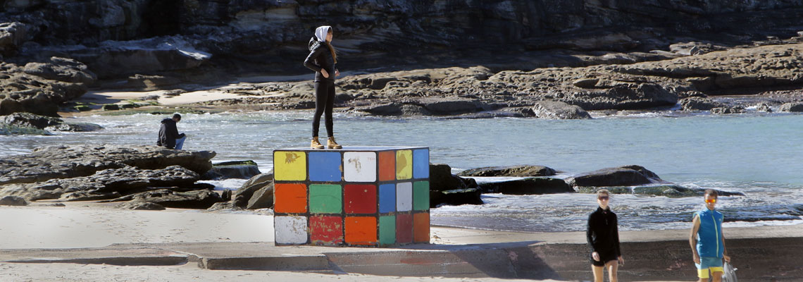 A woman standing upon a large sculpture of a Rubik's Cube on Maroubra beach.