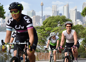 Three cyclists riding on a street on the north side of Sydney Harbour.