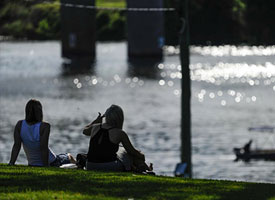 Two women sitting on the grass on the banks of the Nepean River