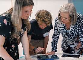 Lucy Turnbull and two teenagers looking at tablet devices