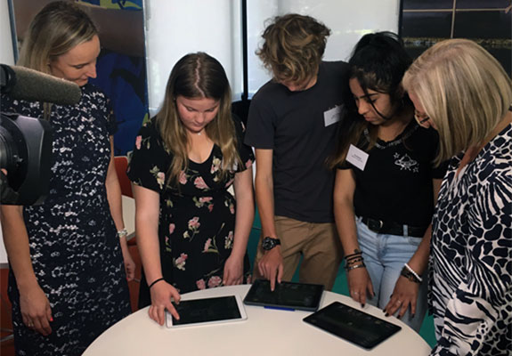 Sarah Hill and Lucy Turnbull looking at iPads with three teenagers