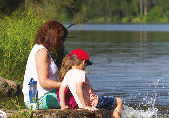 Lady fishing with kids on a river