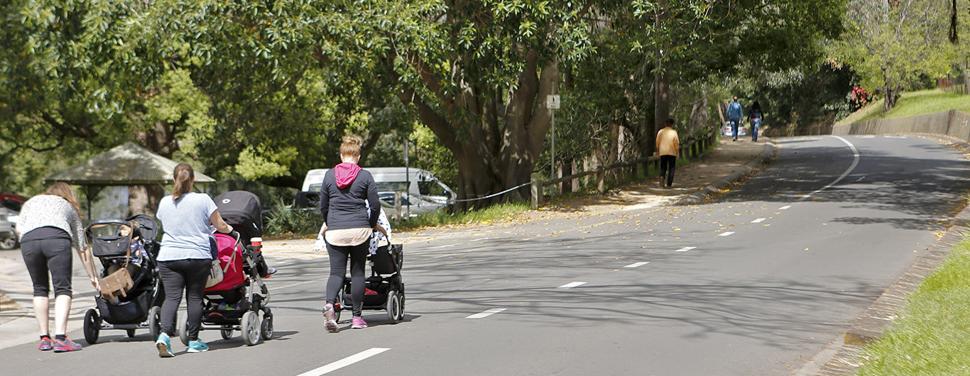 A photograph of women pushing prams in a shaded public open space.
