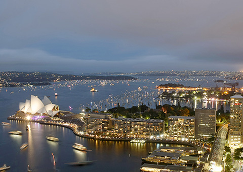Photo of Sydney Harbour at night, looking across Circular Quay and the Sydney Opera House towards the Heads.