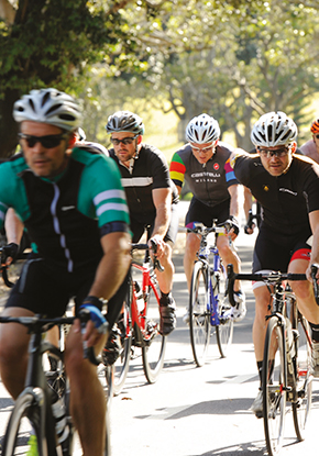 Photo of four male cyclists riding in Centennial Park.