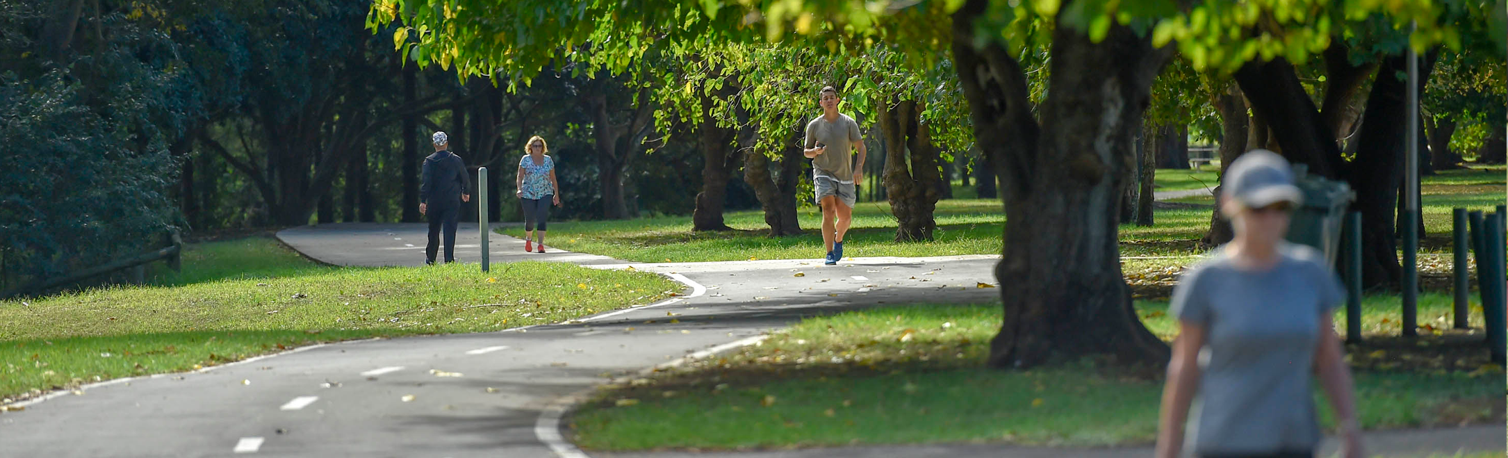 People walking and jogging through a park in Western Sydney.