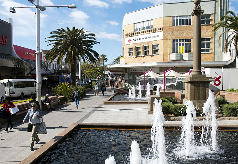 Person walking past water fountain in town centre in Hurstville