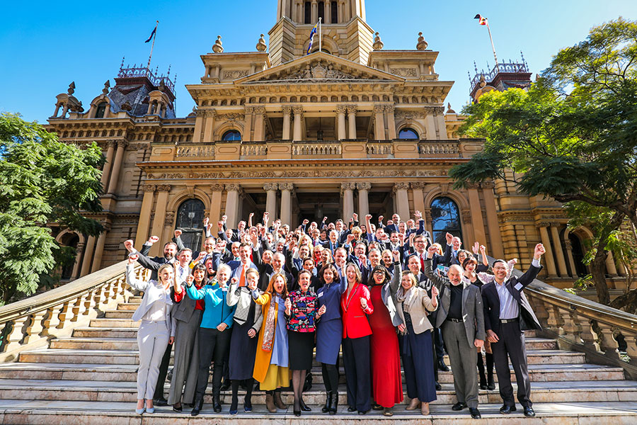 A large group of people standing on the steps in front of Sydney Town Hall