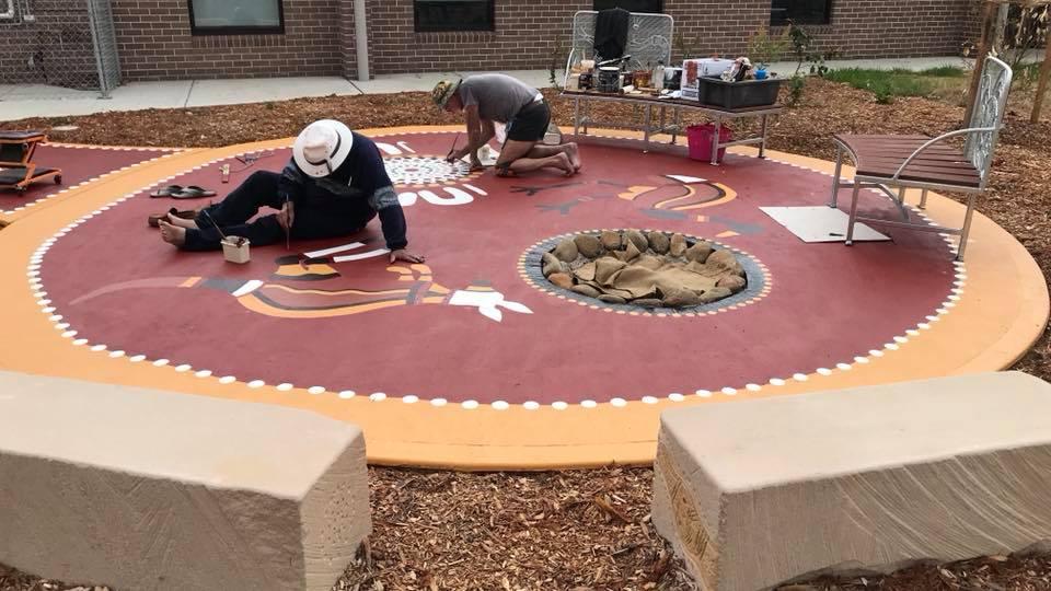 People painting artwork on a garden floor