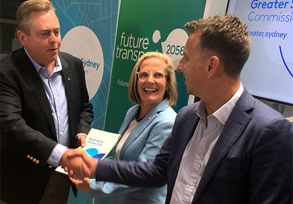 Anthony Roberts and Andrew Constance shaking hands in front of Lucy Turnbull