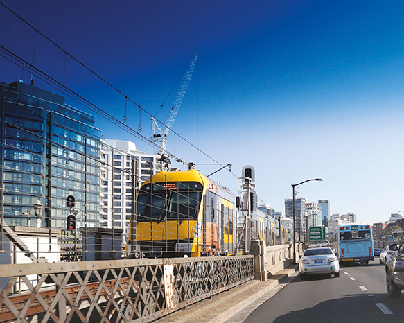 A photograph of a city-bound train crossing the Harbour Bridge from Milsons Point.