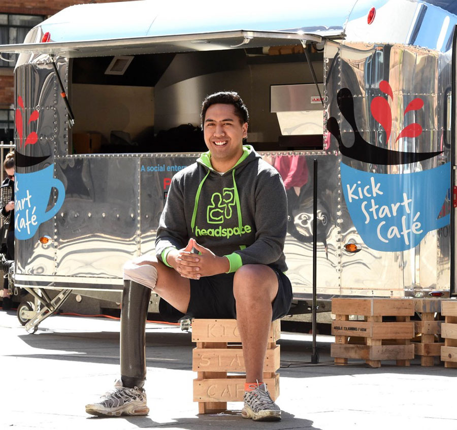 A man sitting on a crate in front of the Kick Start Cafe