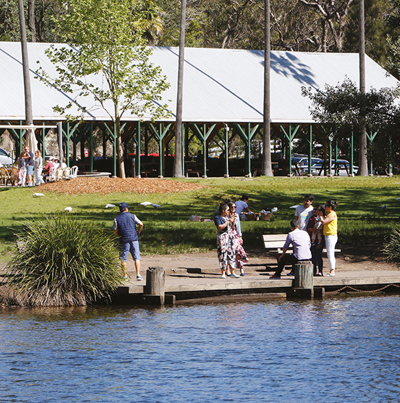 A photograph of people relaxing by a lake in the Royal National Park.