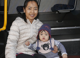 A woman and young girl sitting on the steps of a Talk bus.